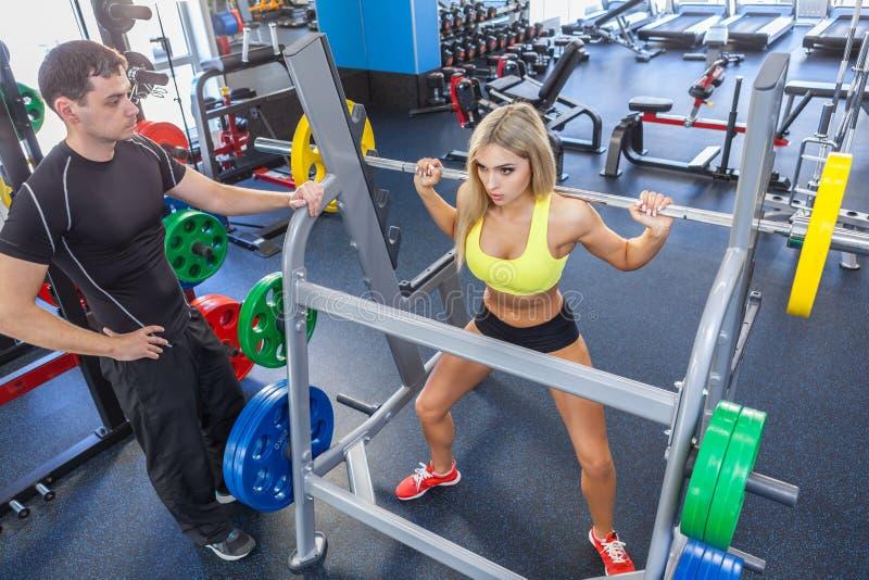Mulher da aptidão e instrutor pessoal no gym fotografia de stock