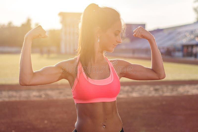 Mulher da aptidão no estádio que mostra fora os braços musculares que dobram os bíceps fotografia de stock