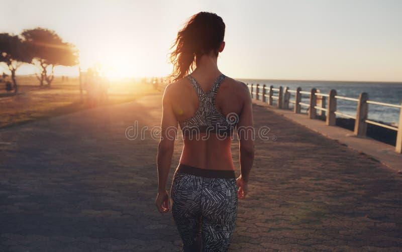 Mulher da aptidão que anda em um passeio do beira-mar no por do sol foto de stock