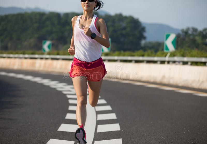 Mulher da aptidão que corre na estrada da estrada imagem de stock