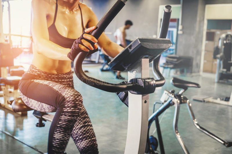 Mulher da aptidão que dá certo na bicicleta de exercício no gym fotografia de stock royalty free