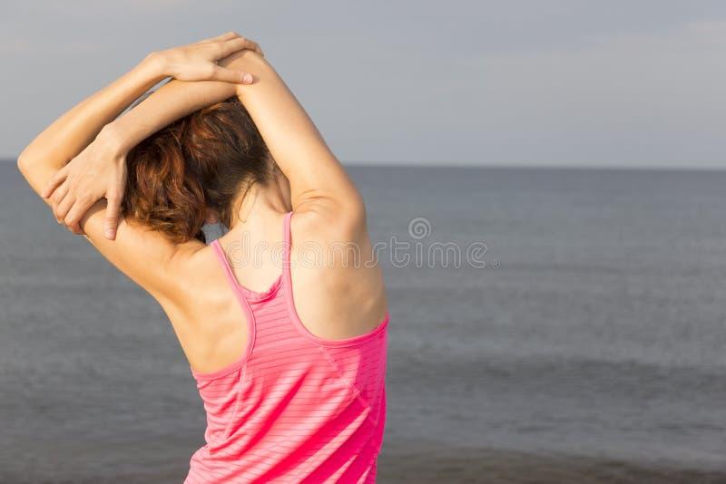 Mulher da aptidão que estica seu tríceps na praia fotografia de stock royalty free