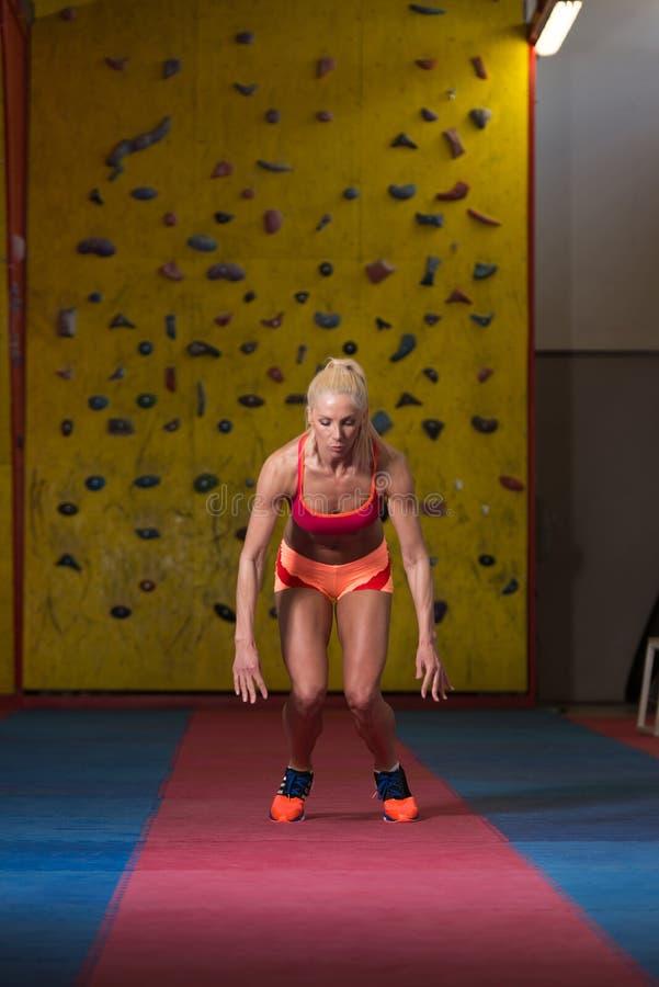 Mulher da aptidão que executa um salto longo no Gym foto de stock