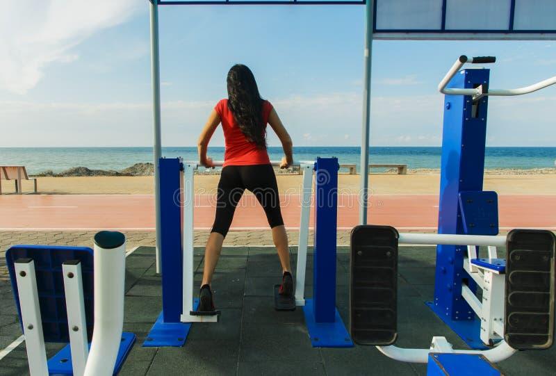 A mulher da aptidão que faz o esporte exercita no gym no ar livre perto do mar fotos de stock