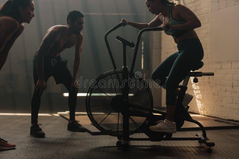 Mulher da aptidão que faz o giro no gym com instrutores imagem de stock