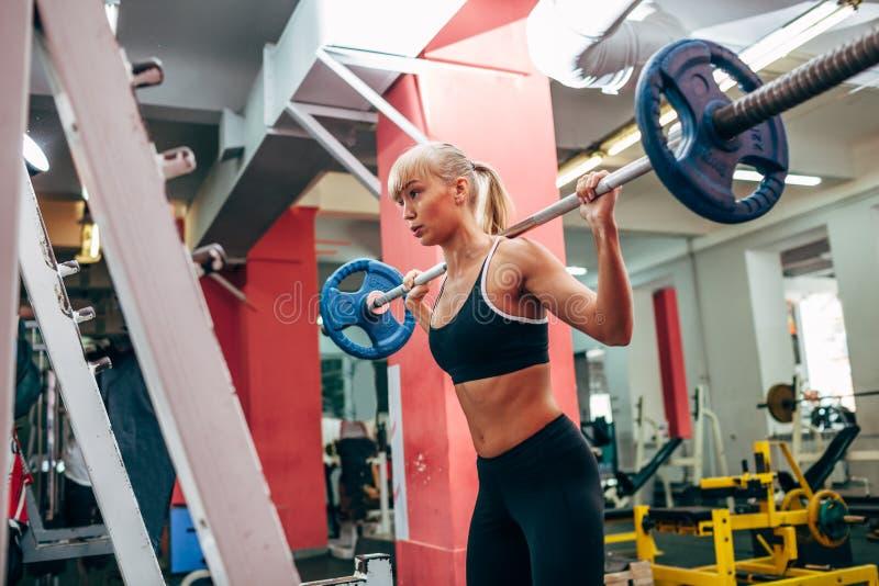 Mulher da aptidão que faz ocupas do barbell em um gym fotos de stock