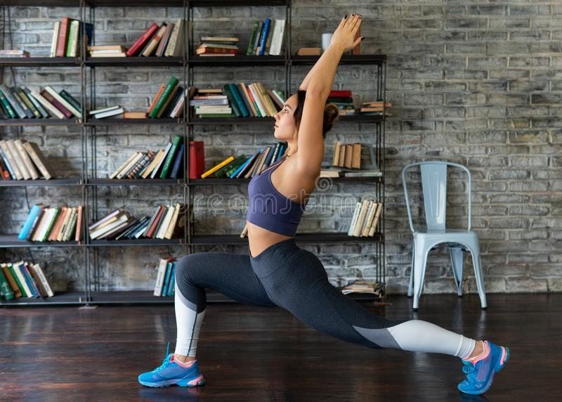 A mulher da aptidão que faz a parte dianteira investe contra durante o exercício da ioga em casa fotografia de stock royalty free