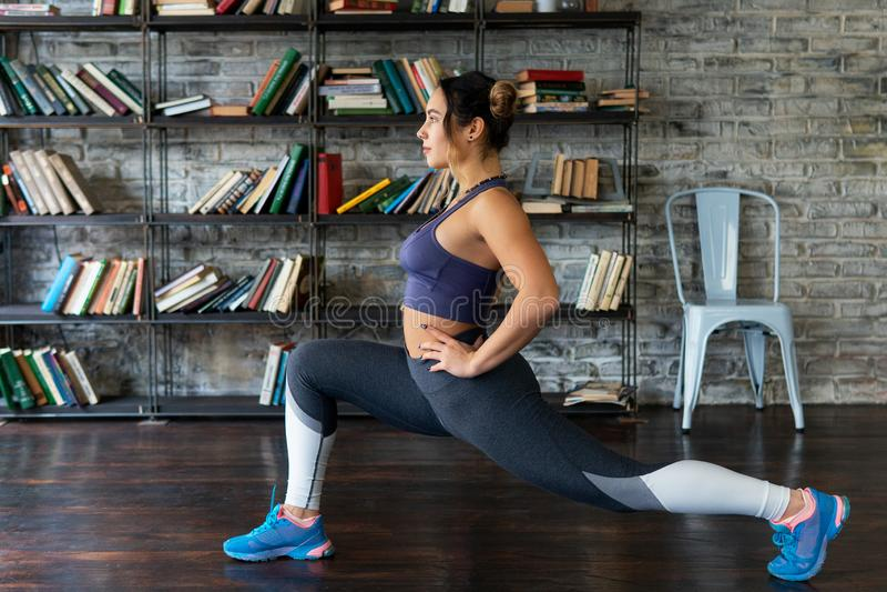 A mulher da aptidão que faz a parte dianteira investe contra o exercício em casa foto de stock royalty free