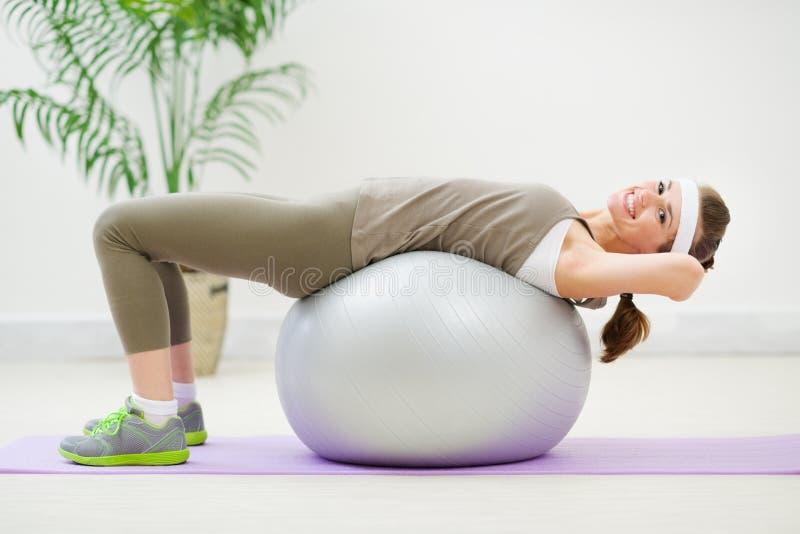 Mulher da aptidão que faz a trituração abdominal na esfera foto de stock royalty free