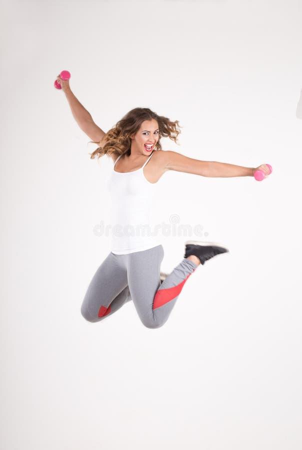 Mulher da aptidão que salta no ar com pesos foto de stock