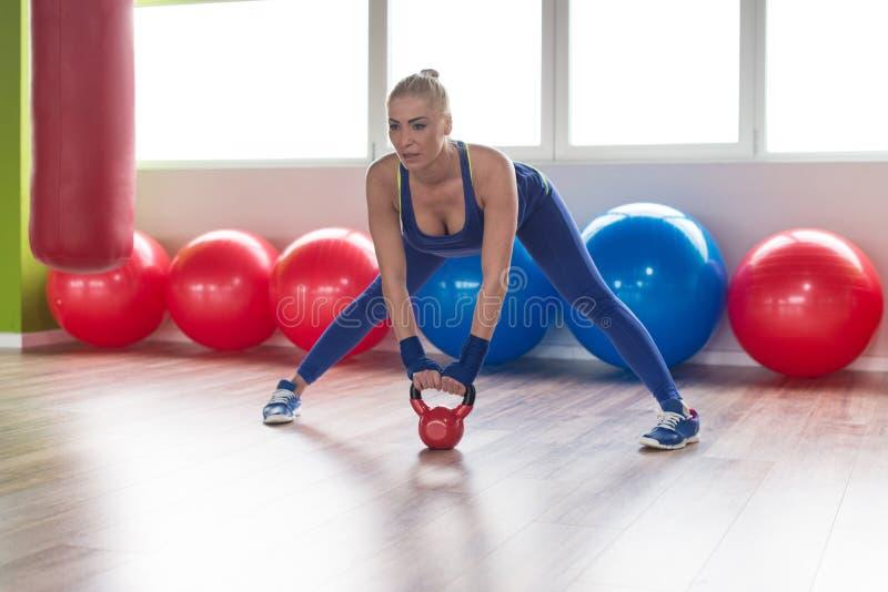 Mulher da aptidão que usa Kettlebells dentro do Gym imagens de stock royalty free
