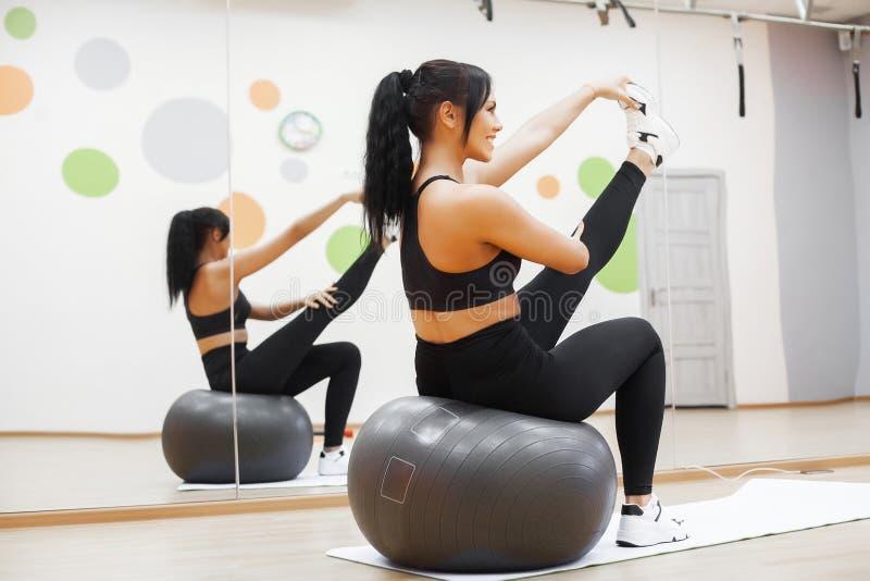 Mulher da aptid?o Mulher atrativa nova que faz exercícios usando a bola imagens de stock royalty free
