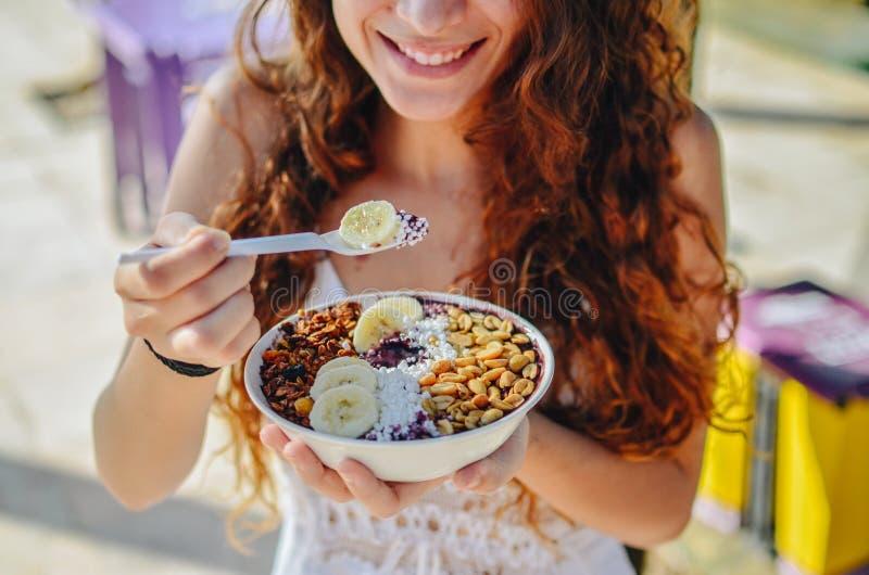 Mulher da bacia de Acai que come o café da manhã da manhã no café Close up da dieta saudável do batido de fruta para a perda de p imagens de stock royalty free