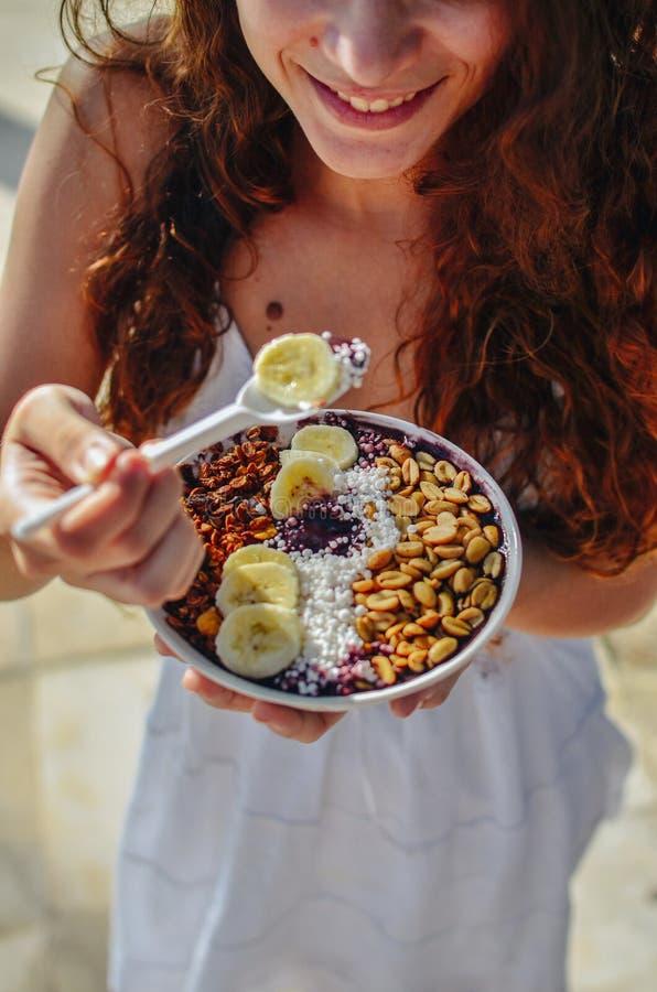 Mulher da bacia de Acai que come o café da manhã da manhã no café Close up da dieta saudável do batido de fruta para a perda de p foto de stock