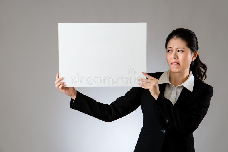 Mulher da bandeira que mantém o quadro de avisos responsabilizado e assustado imagem de stock