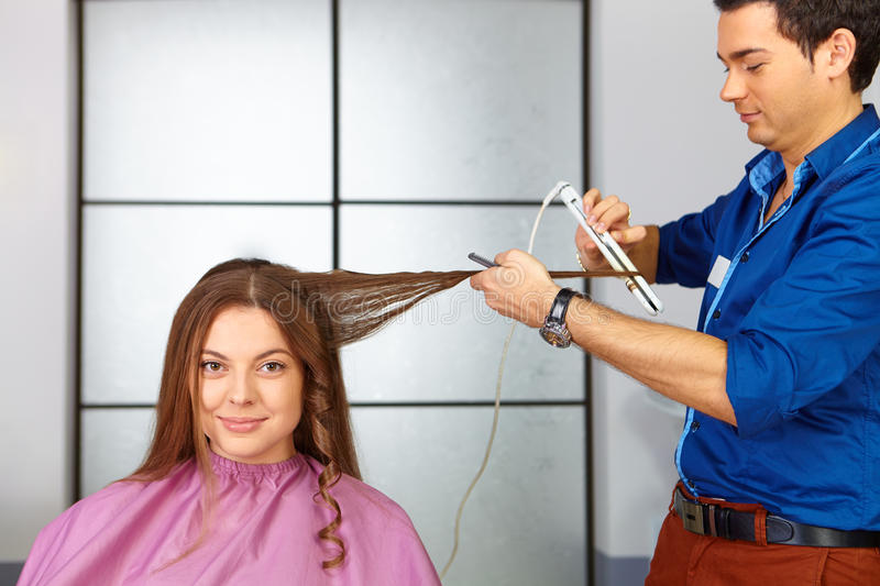 Mulher da beleza com cabelo preto liso saudável e brilhante longo Corte de cabelo da mulher Uso do straightener foto de stock