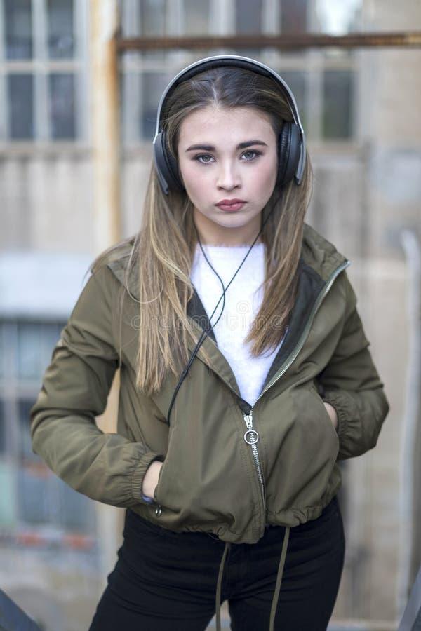Mulher da beleza na música de escuta da roupa morna no fone de ouvido na rua e estar perto da parede fotografia de stock