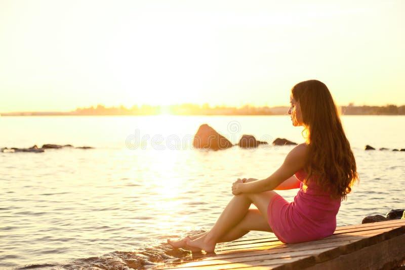 Mulher da beleza na praia no por do sol. Aprecie a natureza. Menina luxuosa r fotografia de stock royalty free