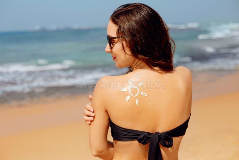 Mulher da beleza que aplica a nata do creme de Sun no ombro bronzeado no formulário de The Sun Prote??o de Sun Cuidado de pele foto de stock royalty free