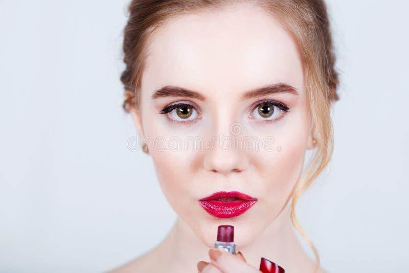 Mulher da beleza que aplica o batom vermelho nos bordos - isolados foto de stock