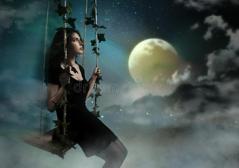 Mulher da beleza que balanç no céu da noite foto de stock