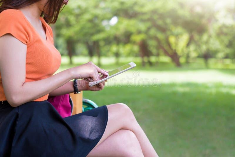 Mulher da beleza que usa a tabuleta no parque Conceito da tecnologia e dos estilos de vida Tema exterior e da natureza foto de stock royalty free
