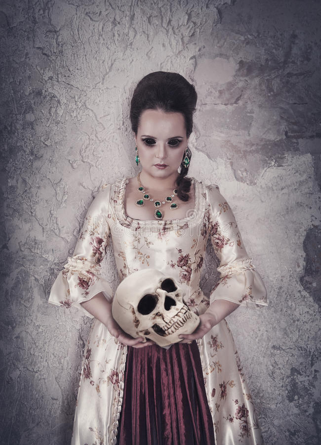 Mulher da bruxa no vestido medieval que guarda o crânio humano nas mãos fotografia de stock