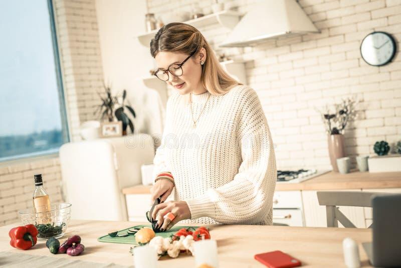 Mulher da calma e do agregado familiar nos vidros claros que cortam vegetarianos fotografia de stock royalty free