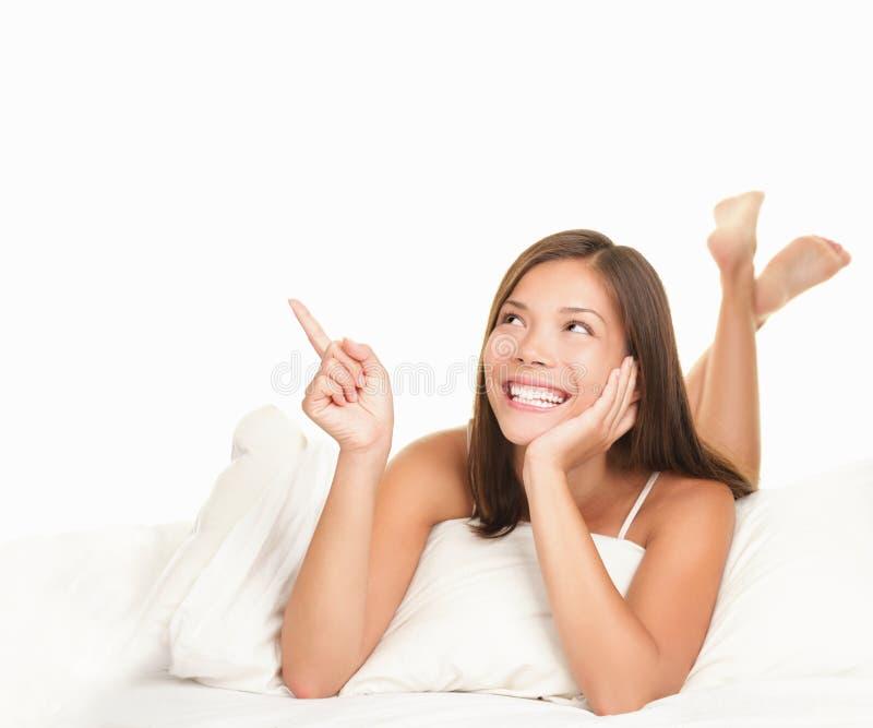 Mulher da cama que aponta acima foto de stock