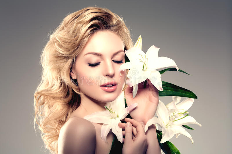 Mulher da cara da beleza, flores, lírio Modelo saudável da menina no salo dos termas imagens de stock