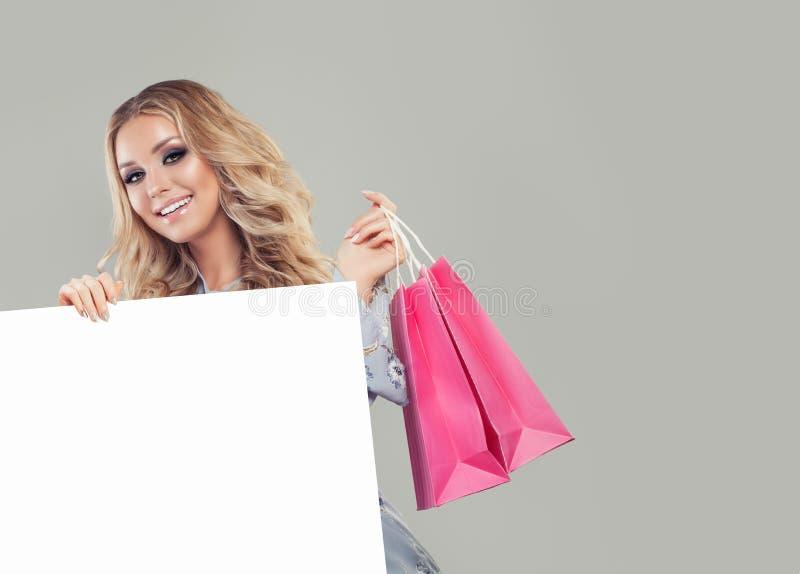 Mulher da compra com sacos e fundo vazio branco da placa imagem de stock royalty free