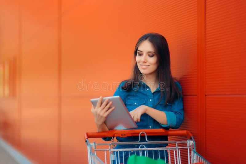 A mulher da compra com tabuleta do PC e o carro de mão próximo armazenam imagem de stock royalty free