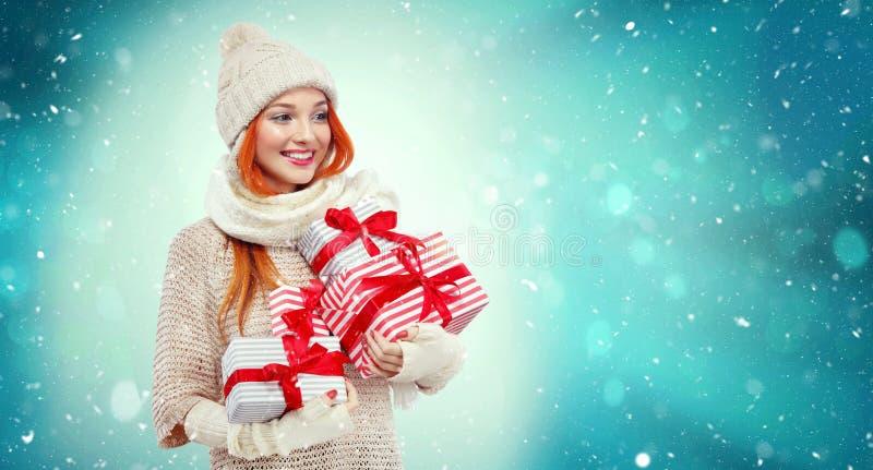 Mulher da compra que guarda caixas de presente no fundo do inverno com neve em sexta-feira, em feriados pretos do Natal e do ano  imagem de stock royalty free