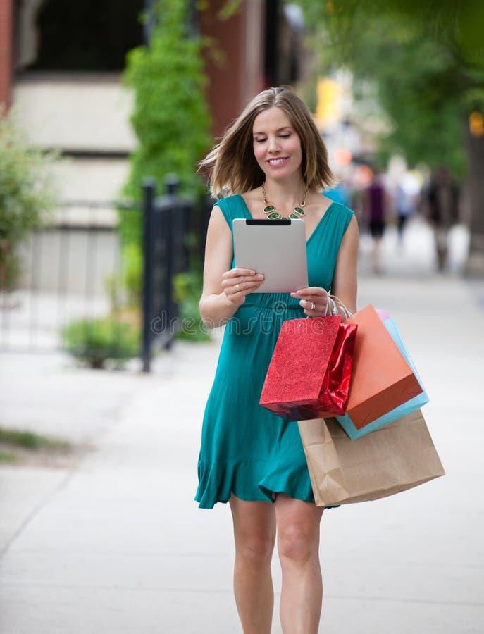 Mulher da compra que guarda a tabuleta de Digitas foto de stock royalty free