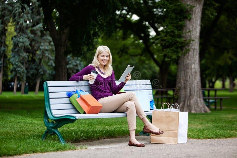 Mulher da compra que usa a tabuleta de Digitas fotos de stock royalty free