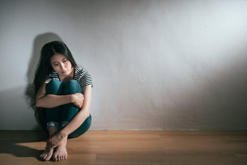Mulher da doença bipolar da depressão que senta-se no assoalho imagem de stock