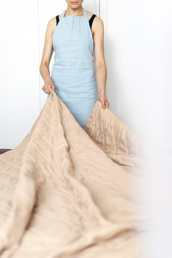 Mulher da empregada doméstica que faz a cama dentro do quarto brilhante e claro imagem de stock royalty free