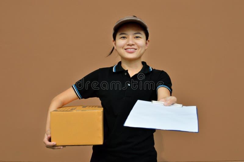 Mulher da entrega no serviço com caixas de cartão e prancheta imagens de stock