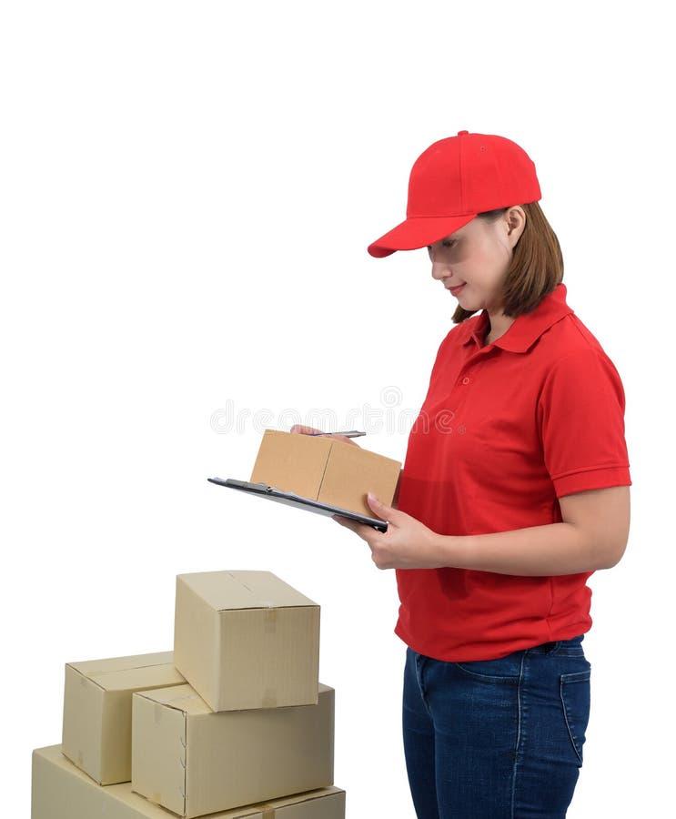 Mulher da entrega no uniforme vermelho com as caixas do pacote que fazem anotações na prancheta do recibo da entrega, isolada no  fotografia de stock royalty free