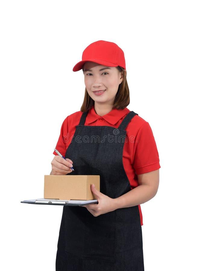 Mulher da entrega no uniforme vermelho com avental e nas caixas do pacote que fazem anotações na prancheta do recibo da entrega,  imagem de stock royalty free