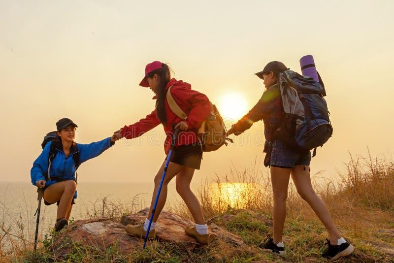 Mulher da equipe do caminhante do grupo que ajuda seu amigo a escalar acima a última seção do por do sol nas montanhas imagens de stock