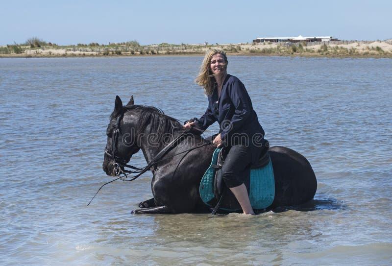 Mulher da equitação na praia fotografia de stock