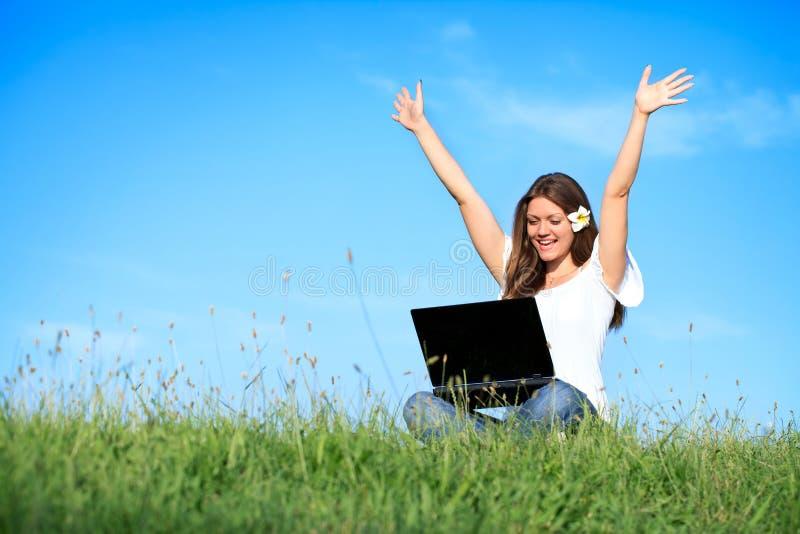 Mulher da felicidade que trabalha com o portátil, ao ar livre imagem de stock