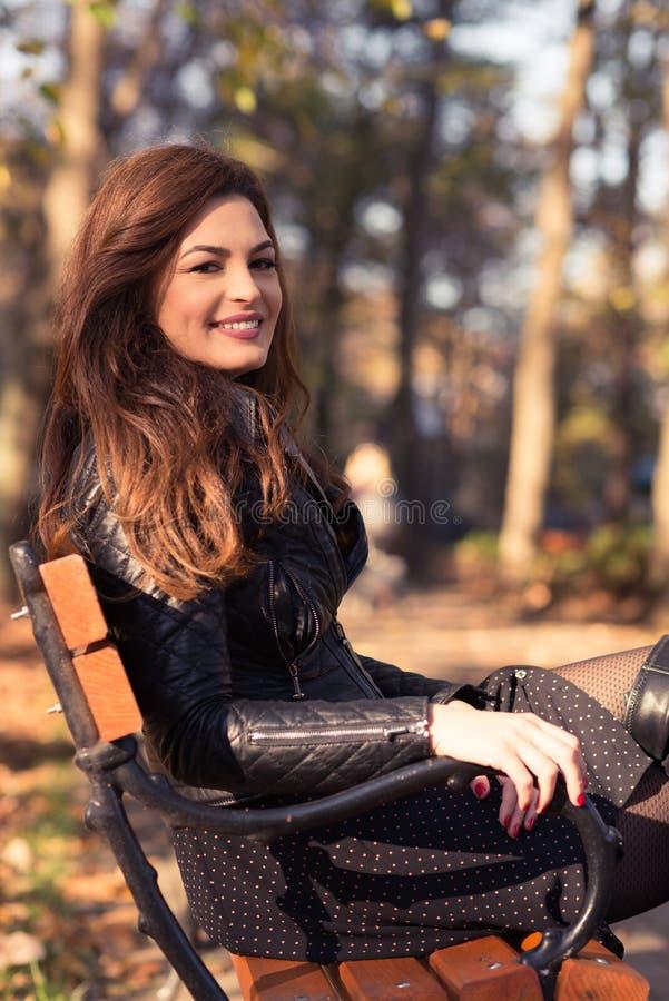 Mulher da forma do outono que senta-se no banco de parque fotografia de stock
