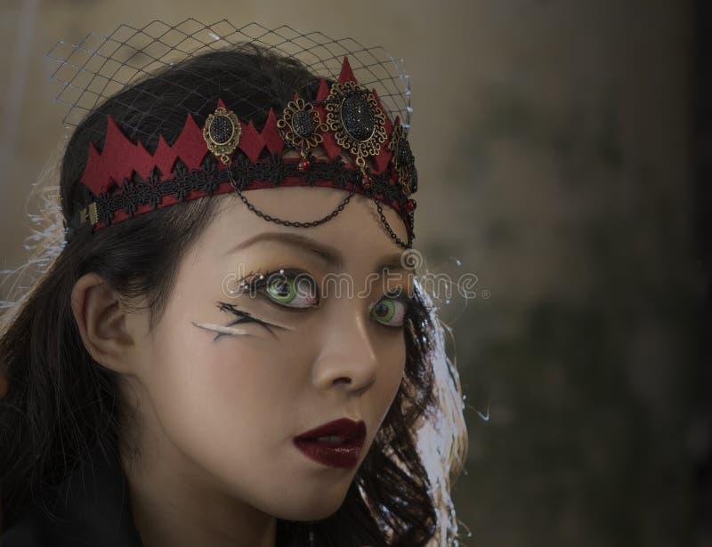 Mulher da forma do vampiro com os olhos verdes do aluno fotografia de stock