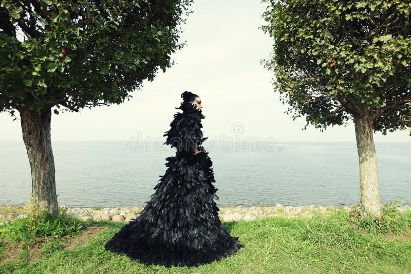 Mulher da forma que levanta perto do mar foto de stock