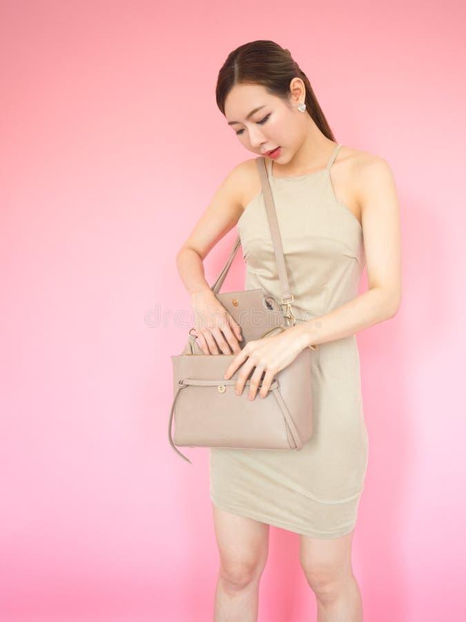 Mulher da forma que olha em sua bolsa de couro imagens de stock royalty free