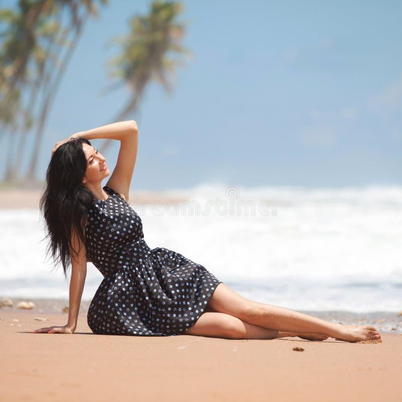 Mulher da forma que relaxa na praia Estilo de vida feliz Areia, c?u nebuloso azul e ondas de oceano F?rias no para?so imagem de stock royalty free