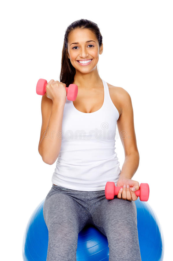 Mulher da ginástica na esfera com dumbbells imagem de stock