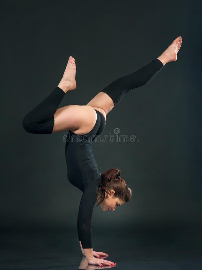 A mulher da ginasta está exercitando no gym no fundo preto imagem de stock